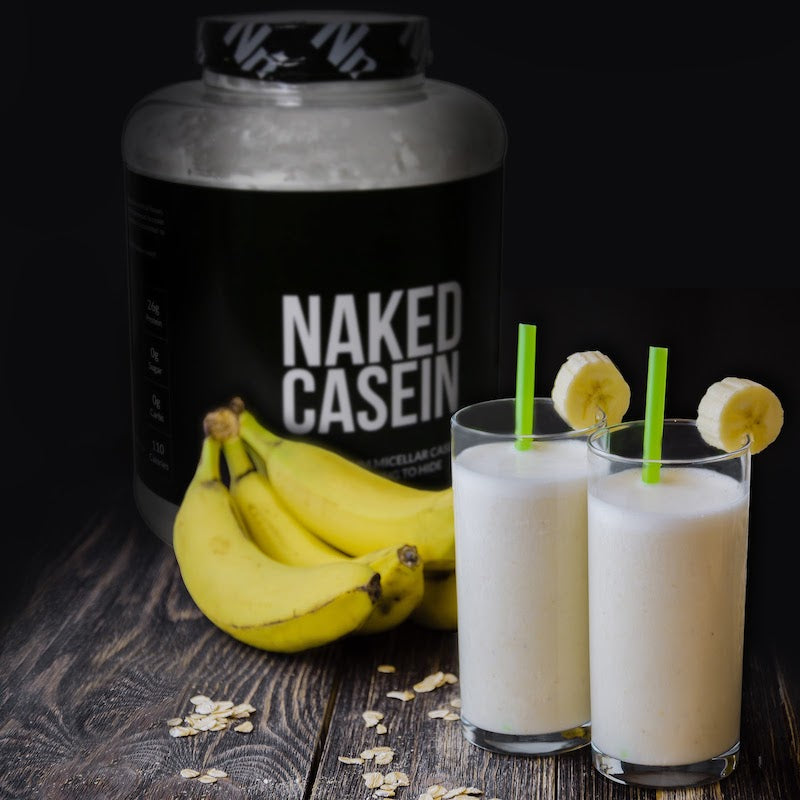 Tub of Naked Casein in the background behind two protein shakes and a bunch of bananas