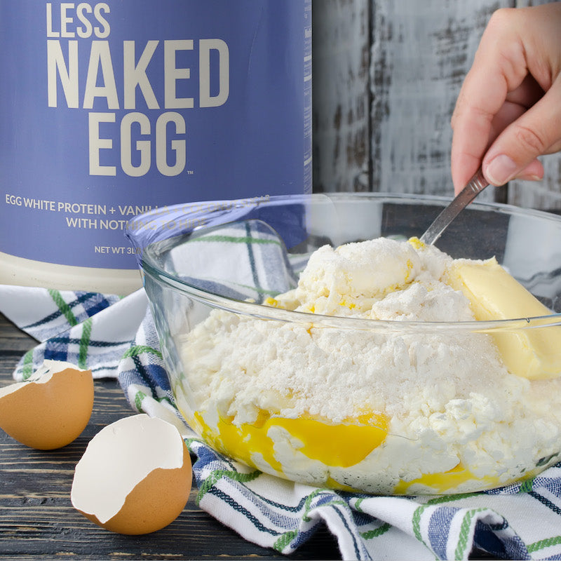 Less Naked Egg product image with a tub of the product behind a bowl with flour and eggs