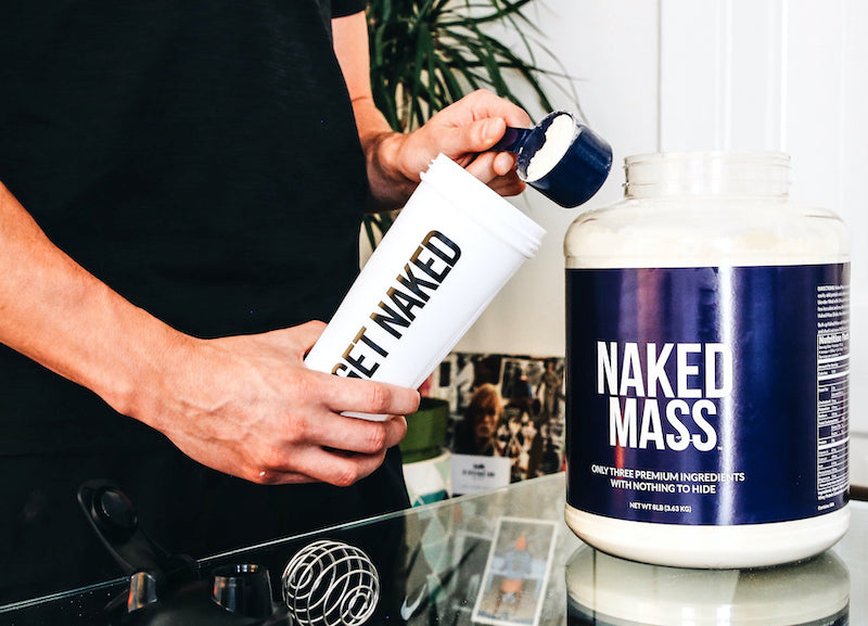 Person putting a scoop of Naked Mass into a Naked Nutrition shaker bottle
