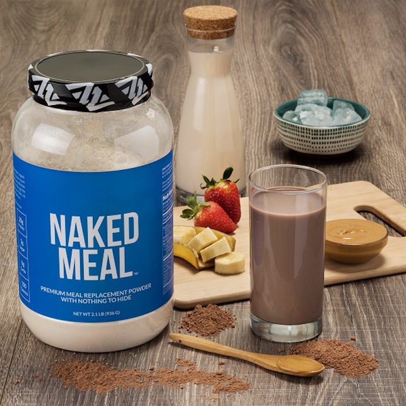 Tub of Naked Meal on a wooden counter beside a meal replacement shake, a glass of milk, and fruit