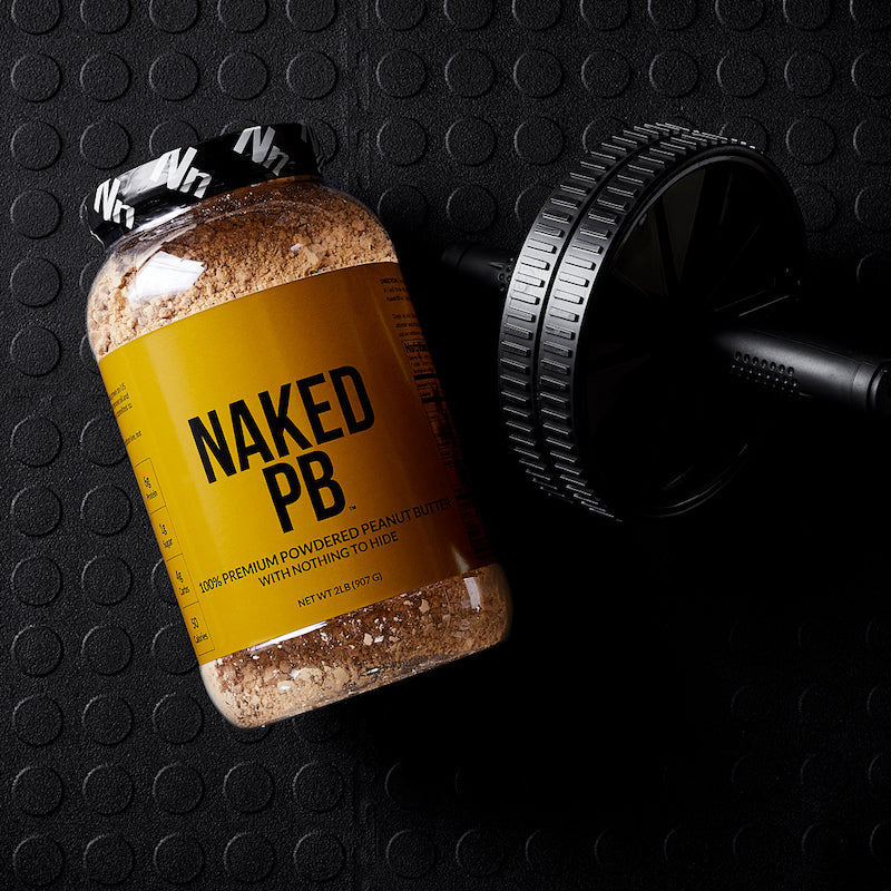 Naked PB product image with a tub of the product on a gym floor next to a weight