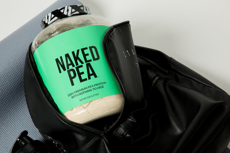 Tub of Unflavord Naked Pea in a black gym bag against a gym mat