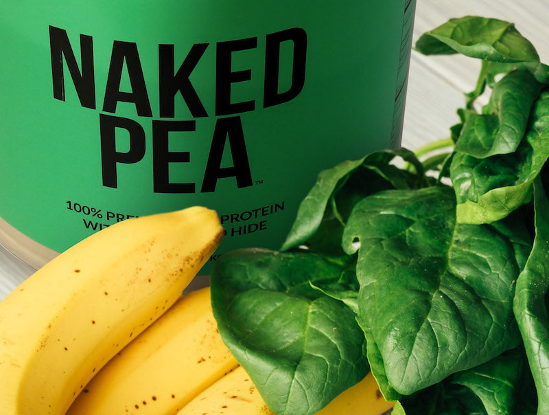 Product image of Naked Pea behind a bunch of bananas and spinach leaves