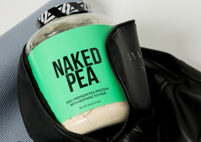 Tub of Naked Pea in a black gym bag leaning against a gym mat