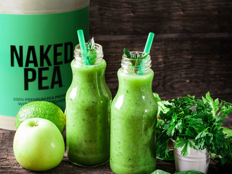 Tub of Naked Pea behind two protein smoothies in glass jars