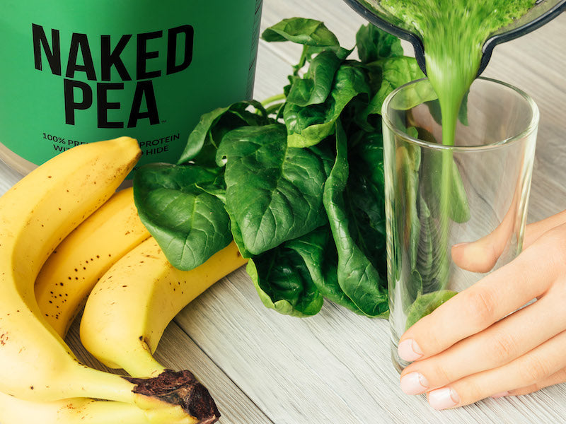 Tub of Naked Pea next to spinach leaves and a bunch of bananas behind a green protein shake being poured in a glass