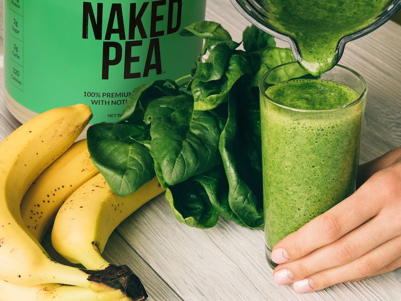 Naked Pea product image with a tub of the product next to a green pea protein shake poured into a glass with spinach leaves and banana