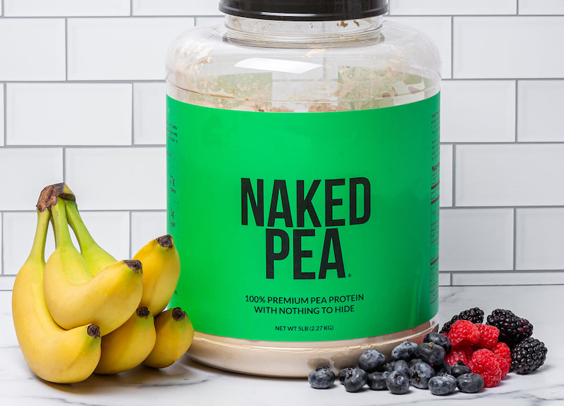 Naked Pea product image with a tub of Naked Pea in front of a white wall and next to berries and bananas