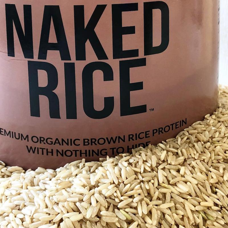 Closeup photo of a tub of Naked Rice, in a pile of raw rice