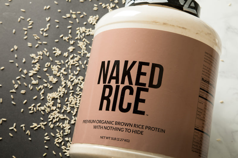 Naked Rice product image with a tub of Naked Rice in front of a white and black background with grains of rice
