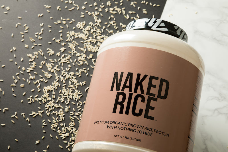 Tub of Unflavored Naked Rice on it's side against a black and white background with loose grains of raw rice around it