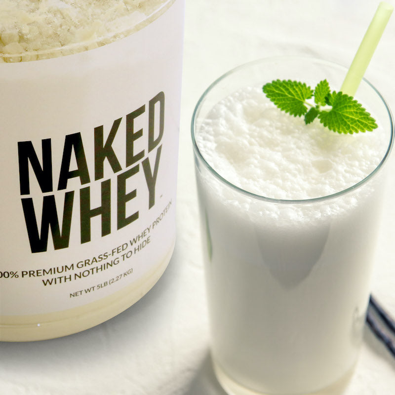 Tub of Naked Whey next to a whey protein shake