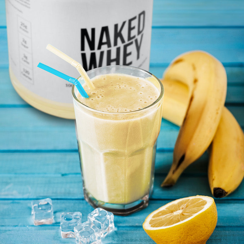 Tub of Unflavored Naked Whey behind a banana protein smoothie on top of a blue wooden table