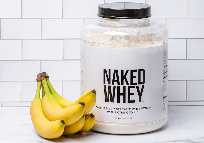 Tub of Naked Whey next to a bunch of bananas in front of a white wall
