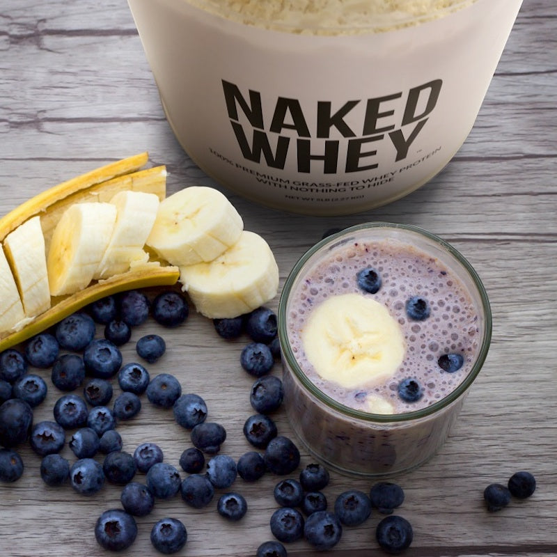 Tub of Unflavored Naked Whey next to a blueberry and banana protein shake in a glass with sliced banana and loose blueberries on the table