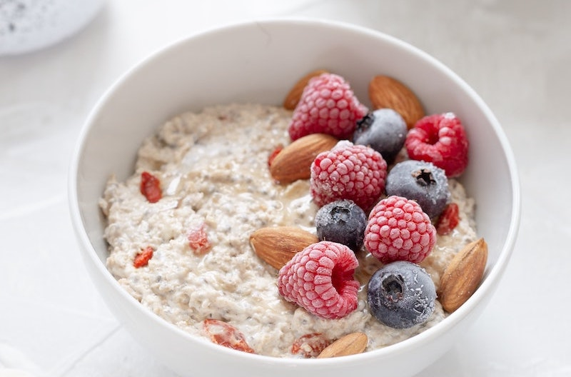 Bowl of oatmeal topped with nuts and berries against a white countertop