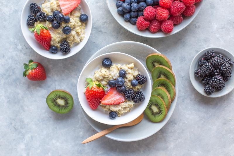 Bowls of oatmeal that are topped with blueberries, strawberries, and paired with slices of kiwi