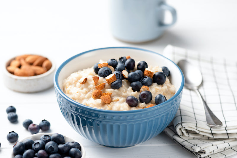 Oatmeal topped with blueberries and nuts in a blue bowl on a breakfast table