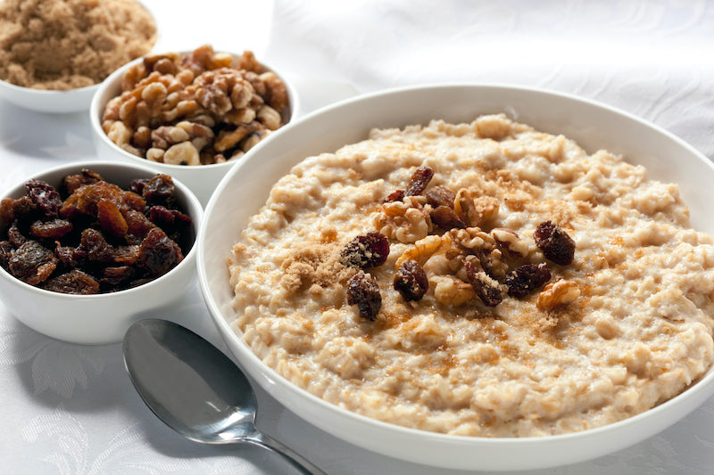 Cooked oatmeal in a bowl, next to smaller bowls of raisins, nuts, and brown sugar