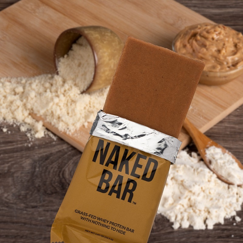 Peanut butter Naked Bar in front of a background of various ingredients