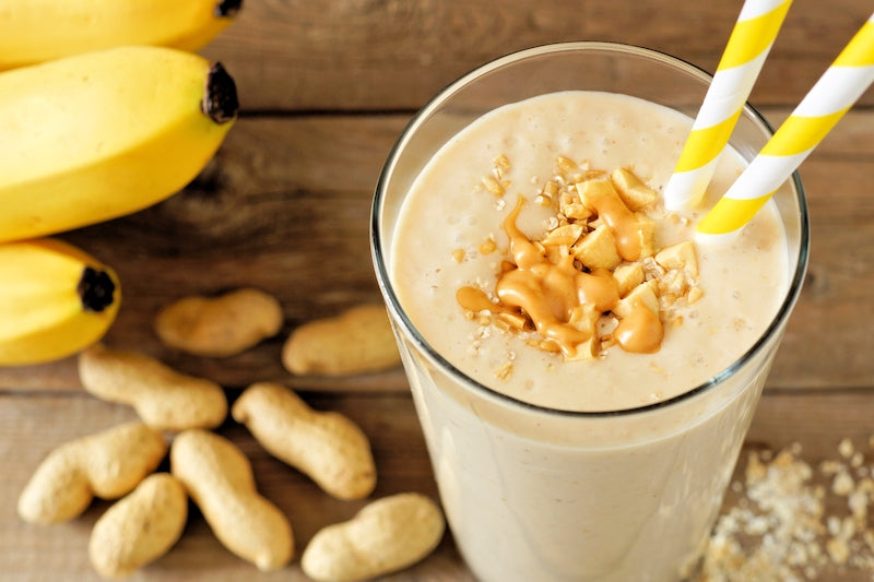 Peanut butter banana smoothie in a glass next to a pile of peanuts and a bunch of bananas