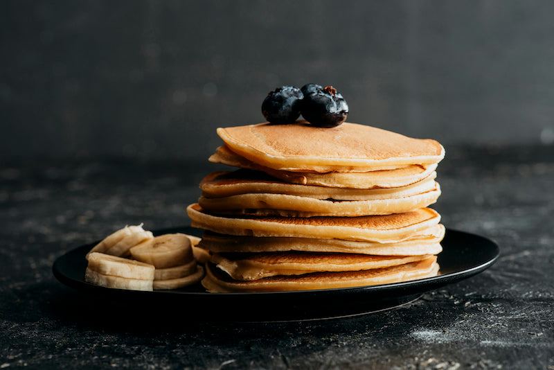 Stack of pancakes with blueberries on top and bananas on the side of the plate