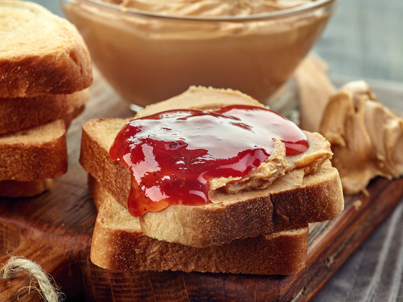 Slices of bread on a chopping board, one is topped with peanut butter and jelly
