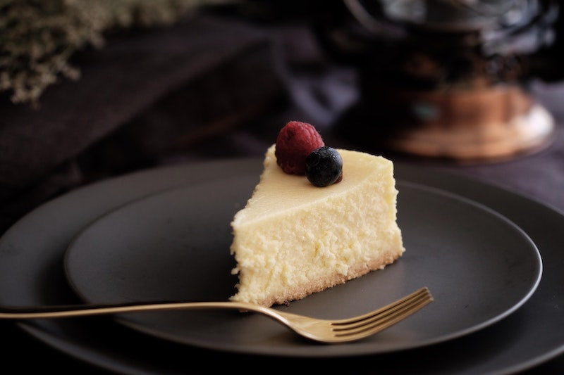 Slice of cheesecake topped with berries on a black plate next to a metal fork