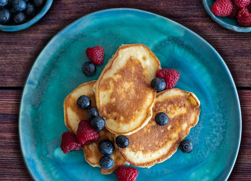 Aerial view of protein pancakes and berries on a blue plate