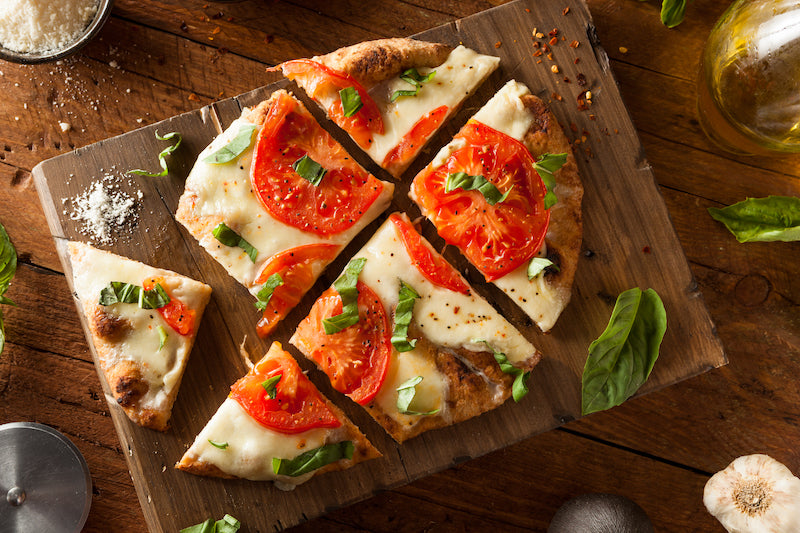 Protein powder pizza topped with mozzarella and tomatoes on a wooden cutting board