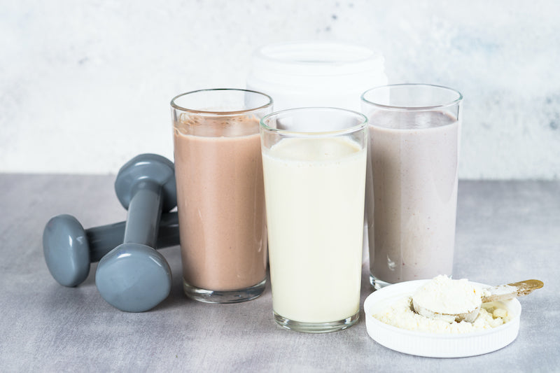 Three flavored whey protein shakes lined up next to a scoop of whey protein and a couple of dumbbells