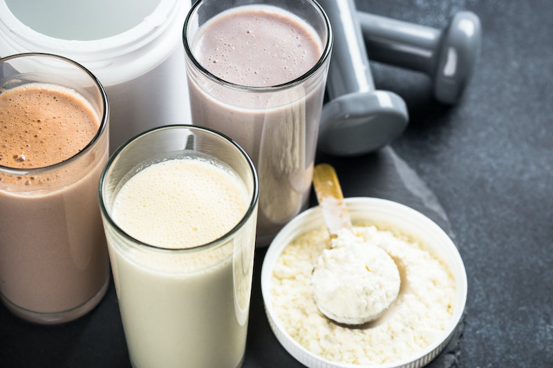 Three different flavored protein shakes next to a tub of protein powder, a scoop of protein powder, and dumbbell weights