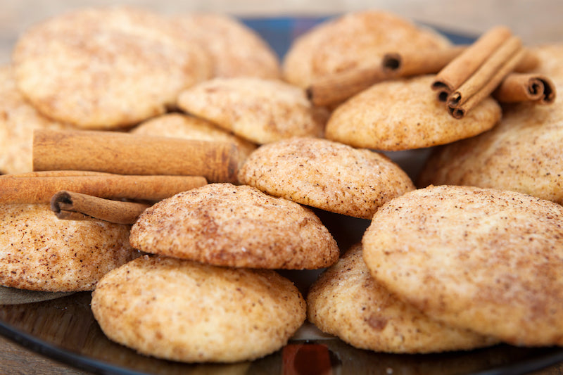 Homemade protein powder snickerdoodle cookies piled up with sticks of cinnamon