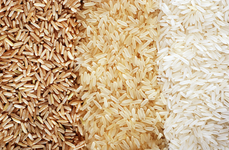 Closeup of three different types of rice in piles next to each other