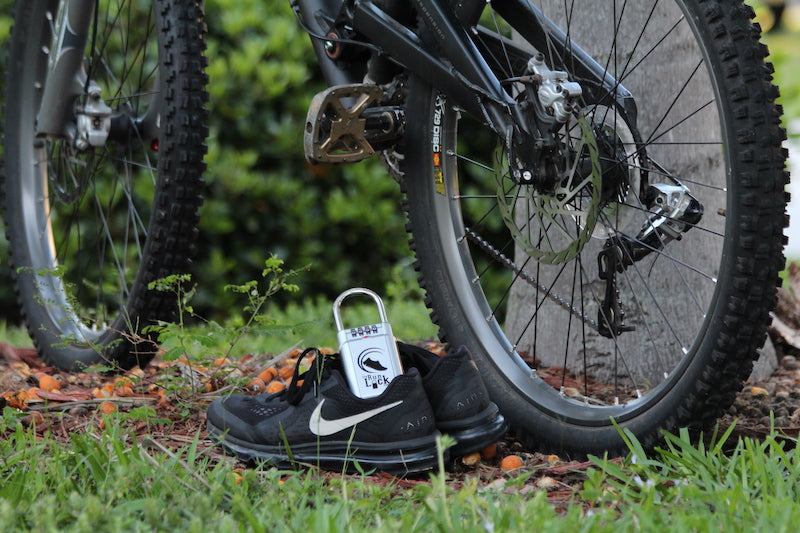 Image of a pair of running shoes next to a bicycle, with the Run Lock in one of the shoes