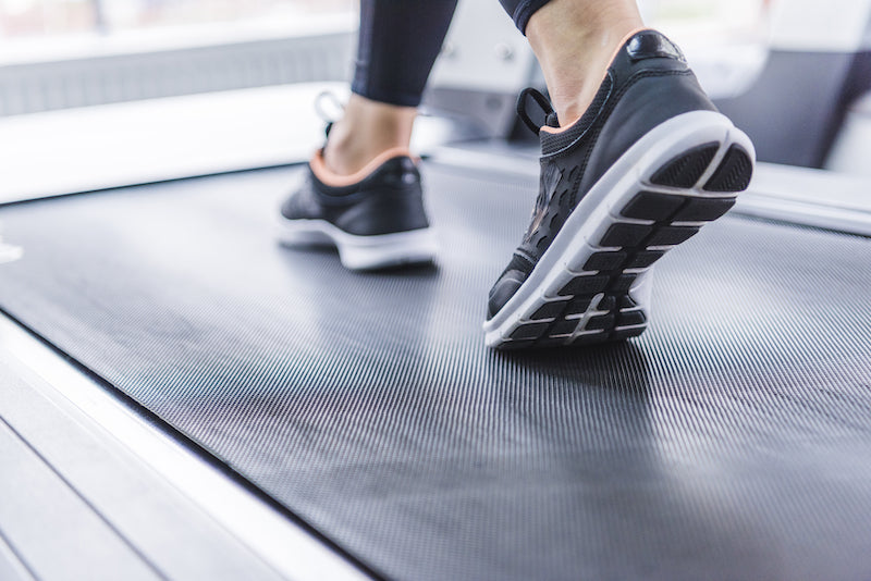 Closeup of the shoes of a woman walking on a treadmill