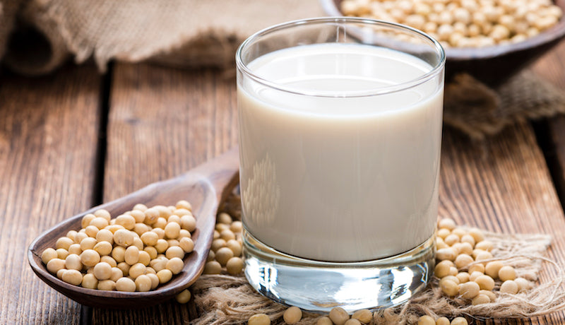 Spoon of soy beans next to a glass of soy milk
