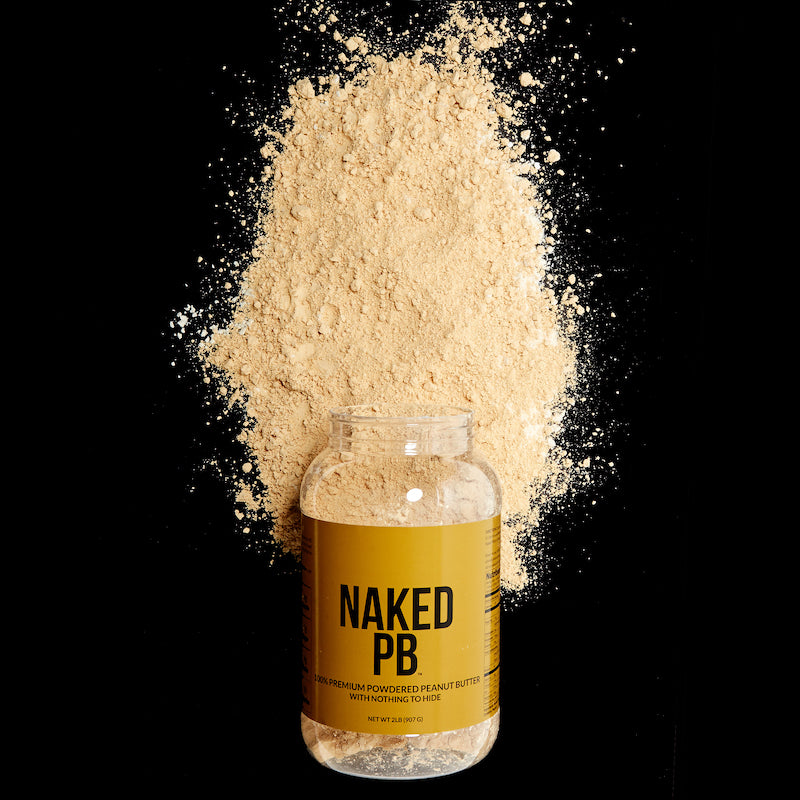 Tub of Naked PB on it's side against a black background with spilt peanut butter powder around it