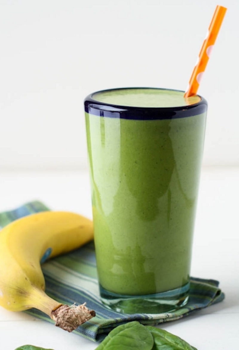 Green pea protein powder shake next to a banana and spinach leaves