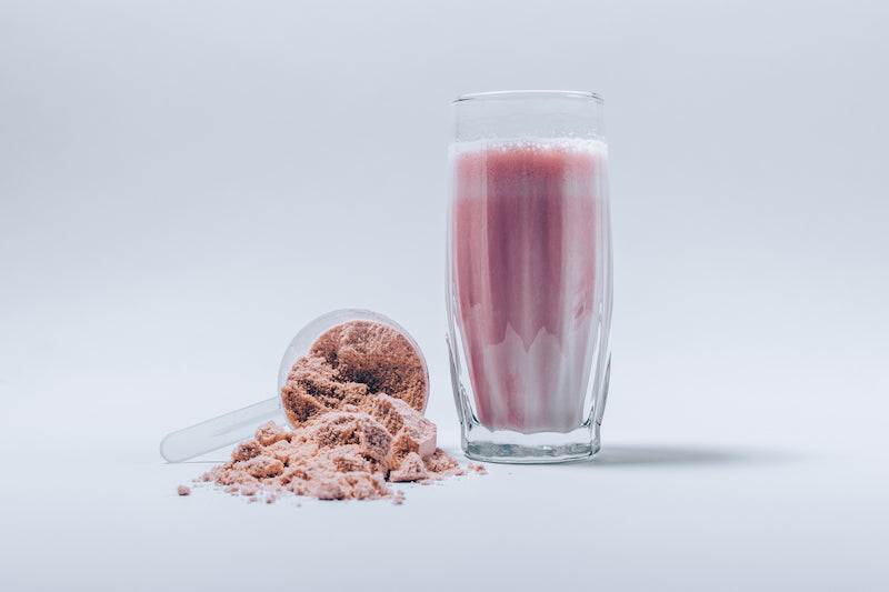Image of a scoop of artificially colored strawberry protein powder next to a strawberry protein shake