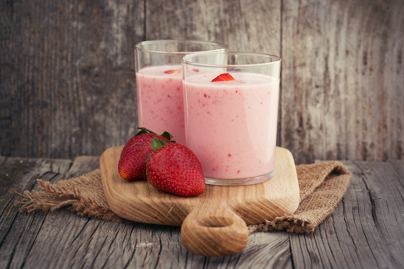 Collagen strawberry smoothies on a wooden board with two strawberries