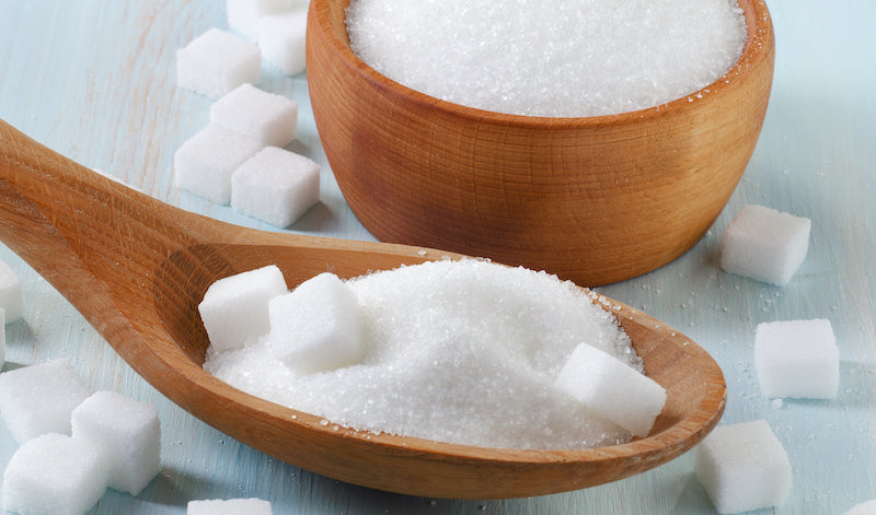 Sugar in a wooden spoon next to a wooden bowl