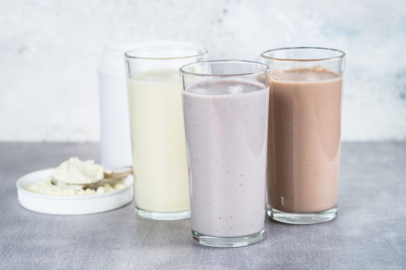 Three differently flavored protein shakes in front of a tub and a scoop of protein powder