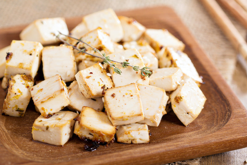 Cubes of tofu on a wooden plate