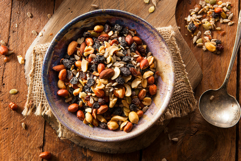 A wooden bowl full of homemade trail mix including nuts and dried berries