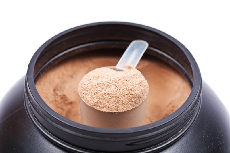 Scoop of protein powder in a tub of protein powder