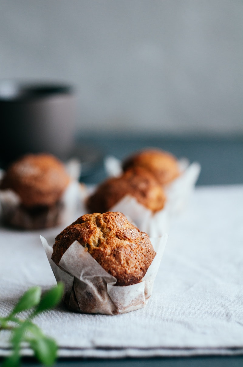 Protein vanilla banana muffins in parchment paper displayed on a table