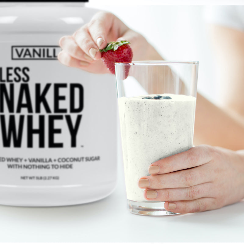 Vanilla Naked Whey product image with the product tub sitting next to a vanilla protein shake, a woman's hands are in frame, placing a strawberry on the glass