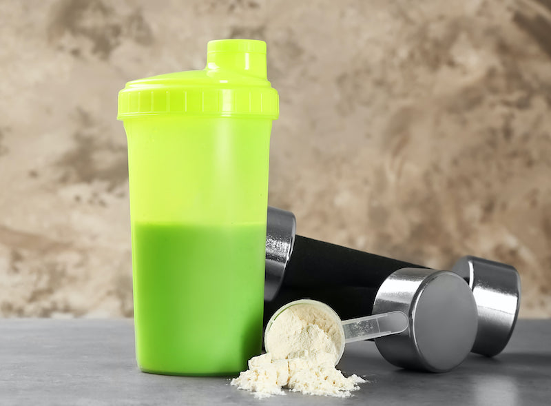 Green shaker bottle next to a scoop of mass gainer powder and a pair of dumbbells on a counter