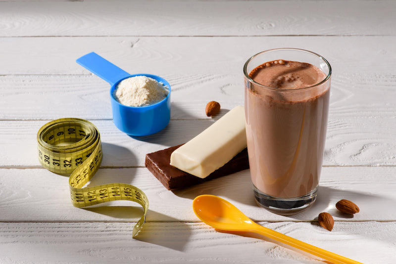 Weight gainer protein shake next to a tape measure, a plastic spoon, two chocolate bars, and a scoop of protein powder